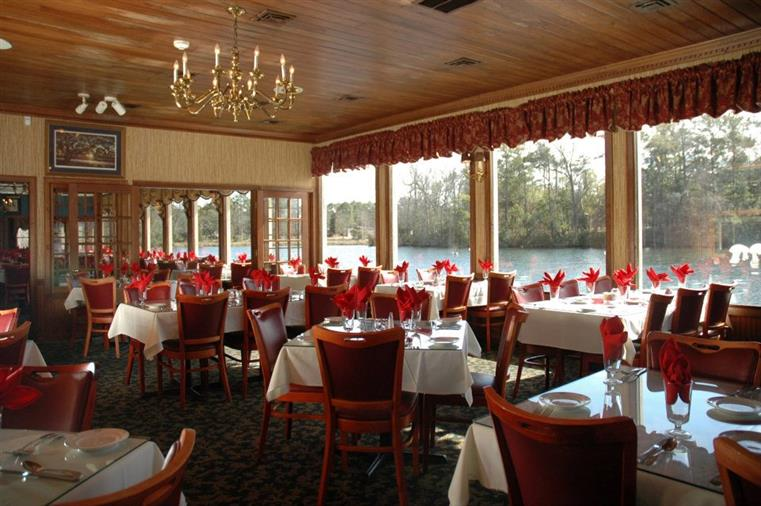 interior dining area of the chestnut hill with multple tables next to an open window showcasing the lake