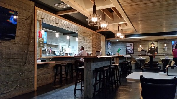 interior dining area with an open area, open kitchen, booths and stools for customers to use