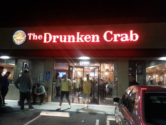 exterior signage hanging for the drunken crab at night time