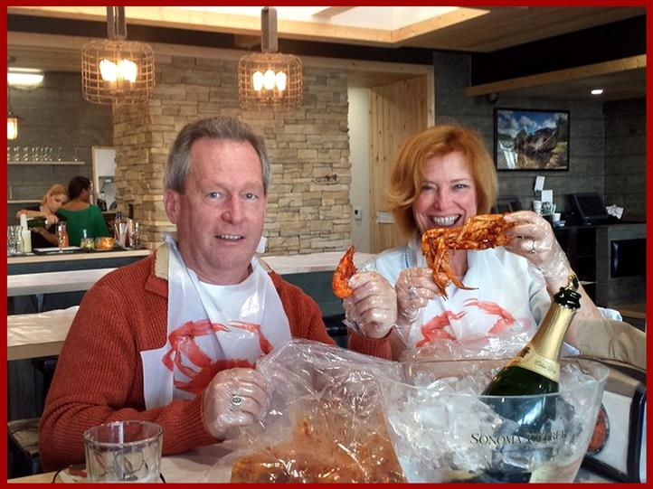 Man and woman in bibs enjoying shrimp and crabs at table with champagne