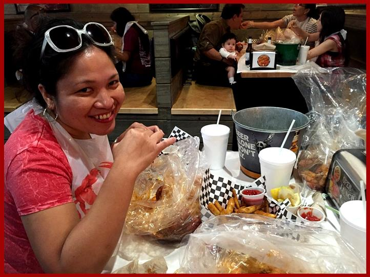 young woman smiling wearing a plastic bib enjoying seafood at a table