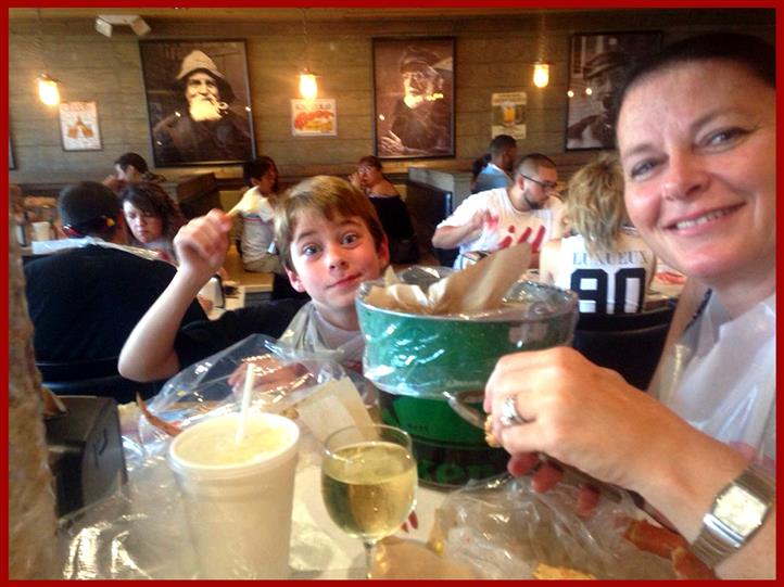 family with kids at a table enjoying a bucket of seafood