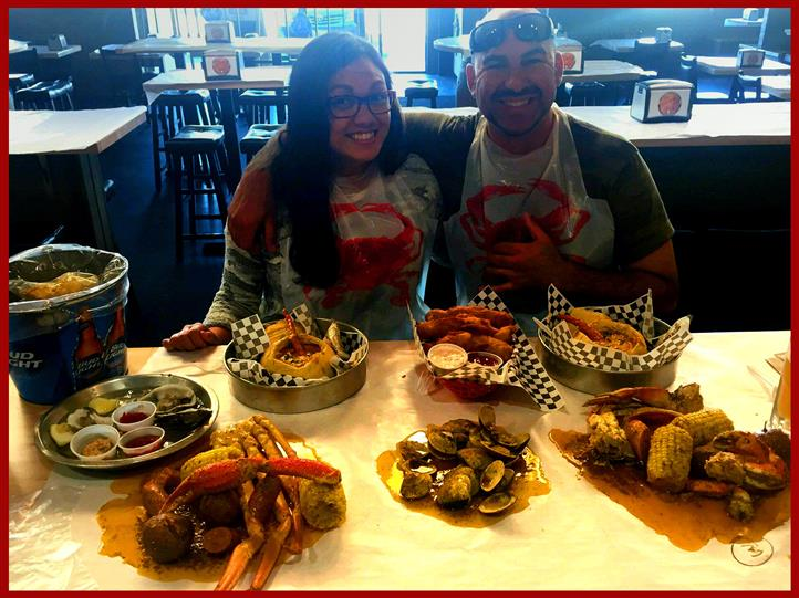 young couple together smiling for the camera behind a table full of various food items
