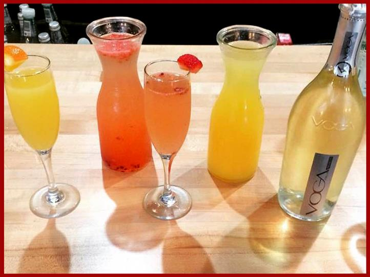 Variety of mixed cocktails and voga bottle on bar top.