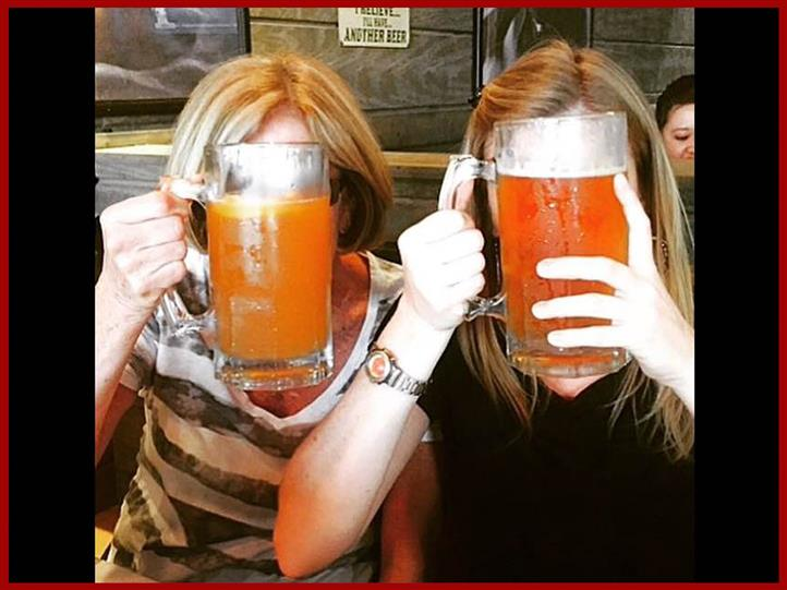 two older woman holding up large pints of beer which are blocking their faces