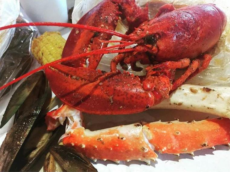 Whole lobster over crab legs, mussels, corn