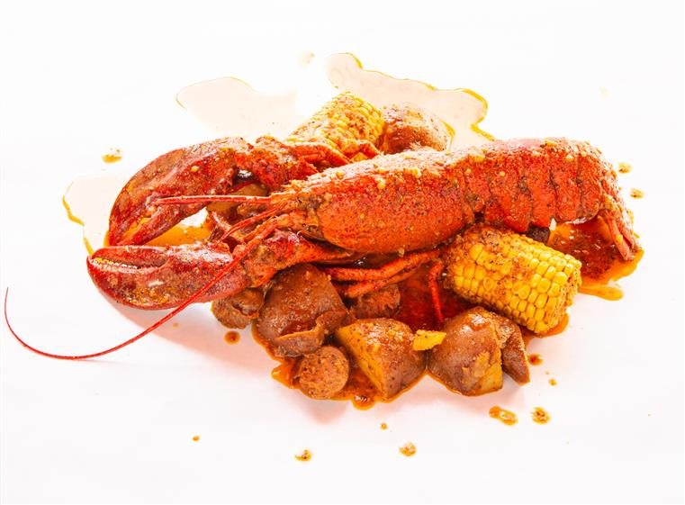 Lobster louisiana style with corn and potatoes.