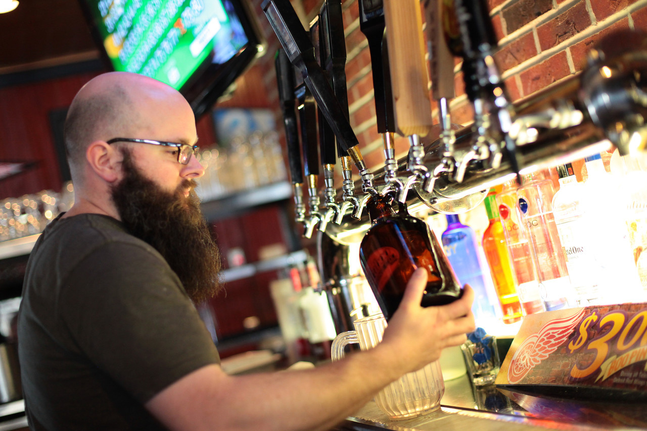 Bartender filling up a growler from a beer tap