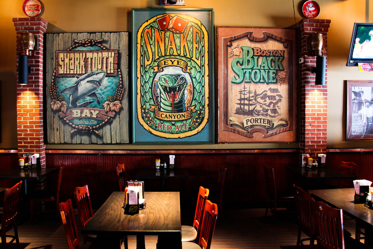Interior dining area with wooden chairs and tables set up with large hand painted beer labels on the wall