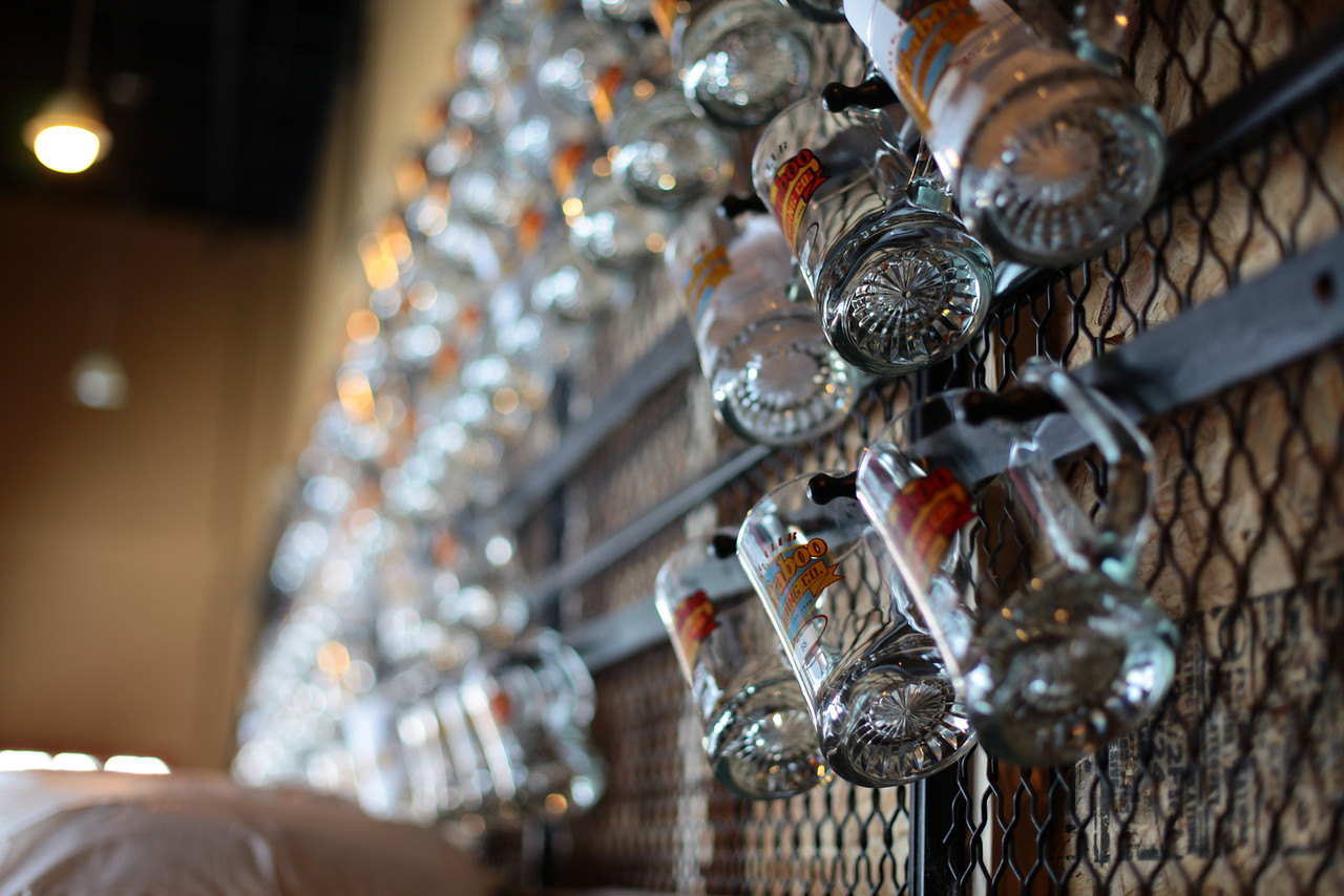 Close-up of glass beer mugs with Great Baraboo Brewing branding hanging on a metal grate