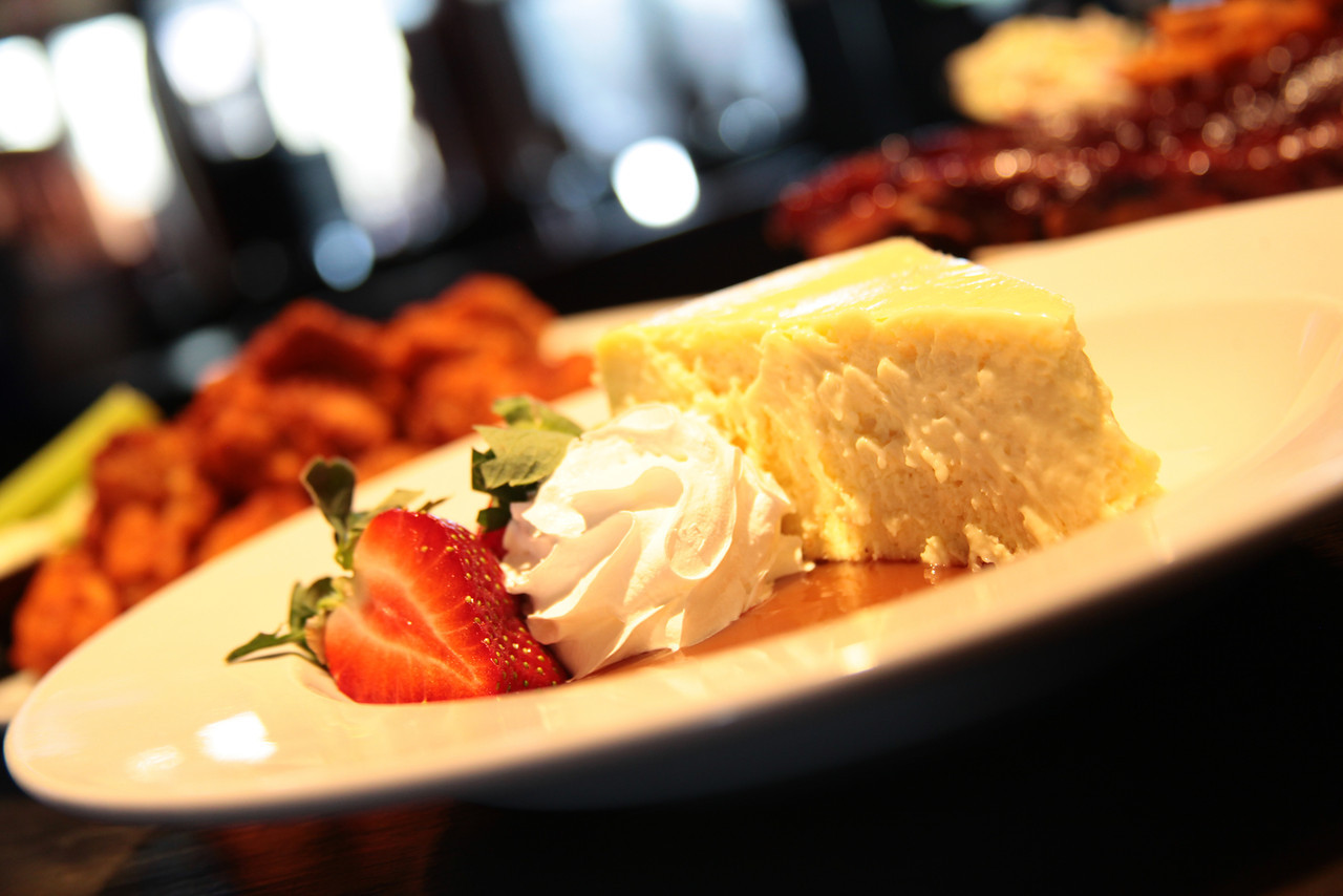 Slice of cheesecake with whipped cream and strawberries