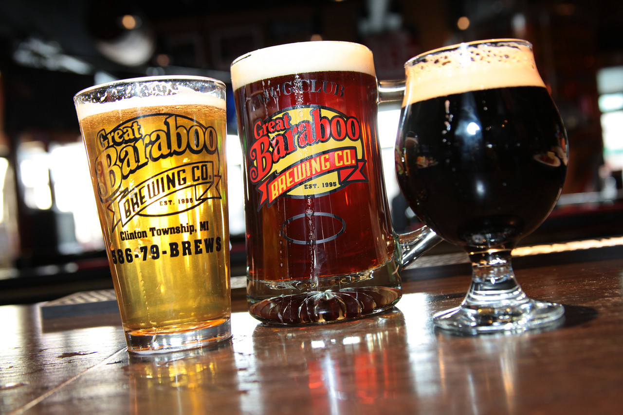 A lite, amber and dark beer in glasses lined up on a counter-top