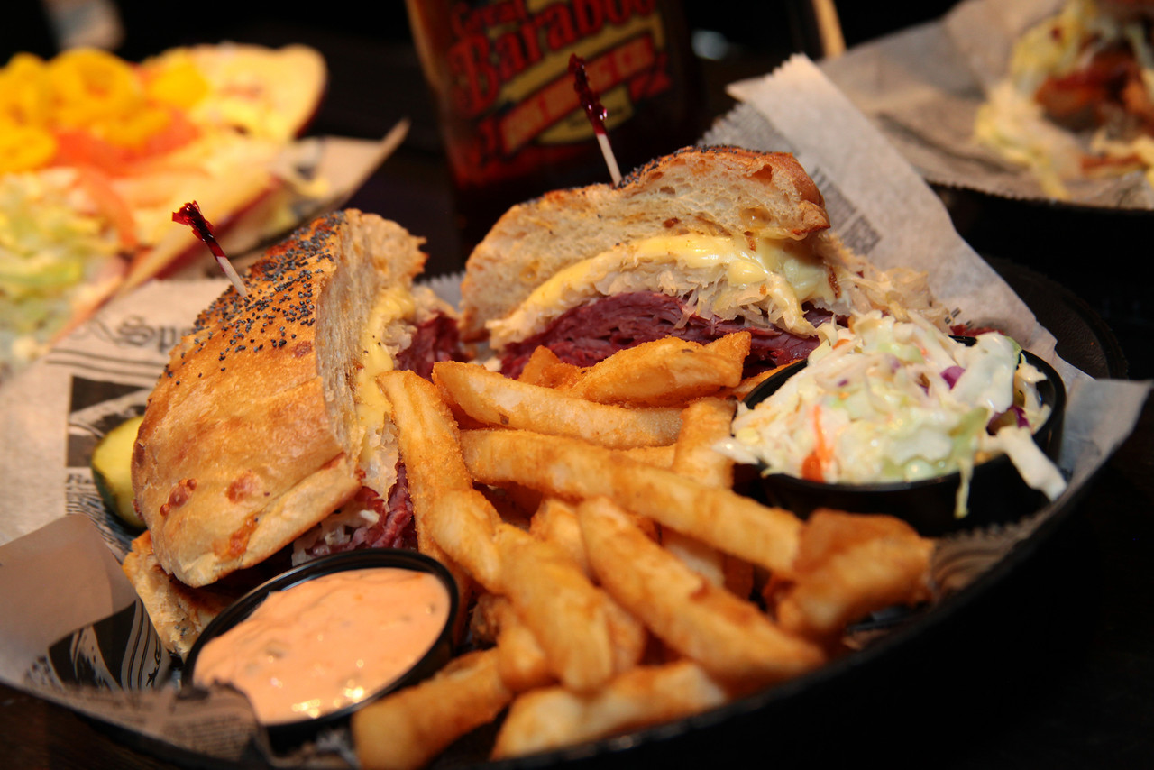 Reuben sandwich with sauerkraut and Russian dressing on a bun with French fries, coleslaw and dipping sauce