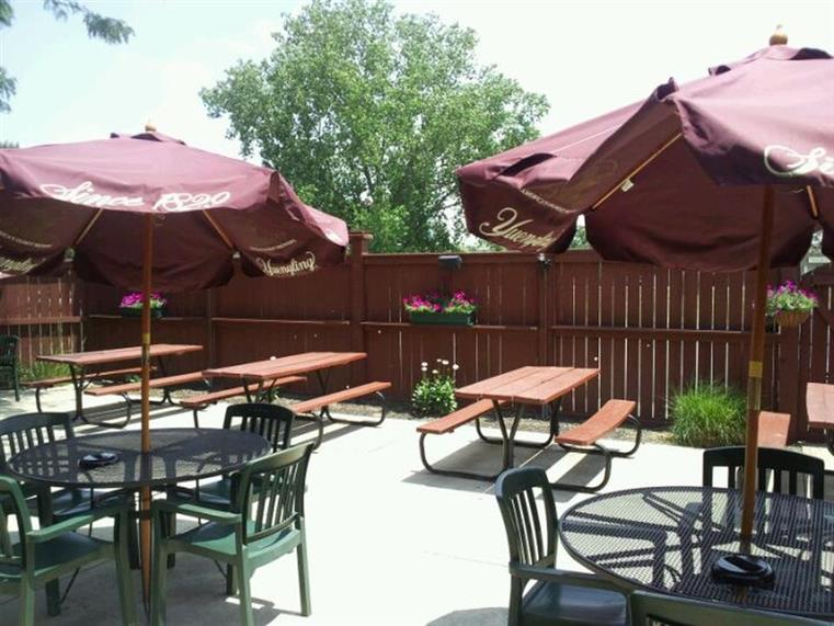 Coaches Bar and Grill outdoor patio with benches, chairs and tables