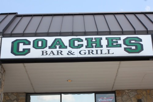 "outside sign displaying ""Coaches Bar and Grill"""