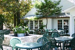 Outside of Dinery with green lawn chairs and tables and greenery