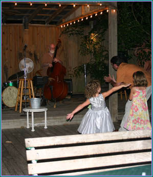 Little girls dancing in front of the stage with the band playing