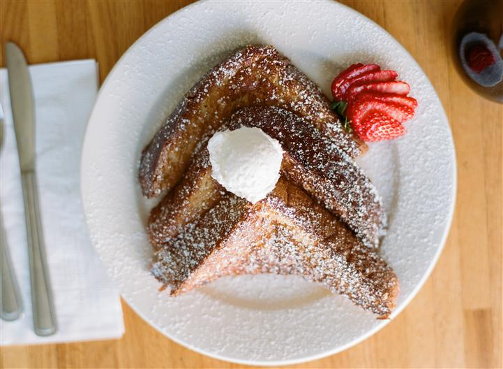 french toast with butter, powered sugar and strawberries