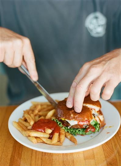 man cutting into a cheeseburger with a side of a fries