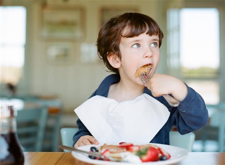 young child eating a plate of pancakes with fresh fruit