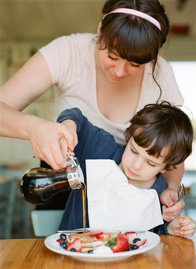 women helping her son pour syrup