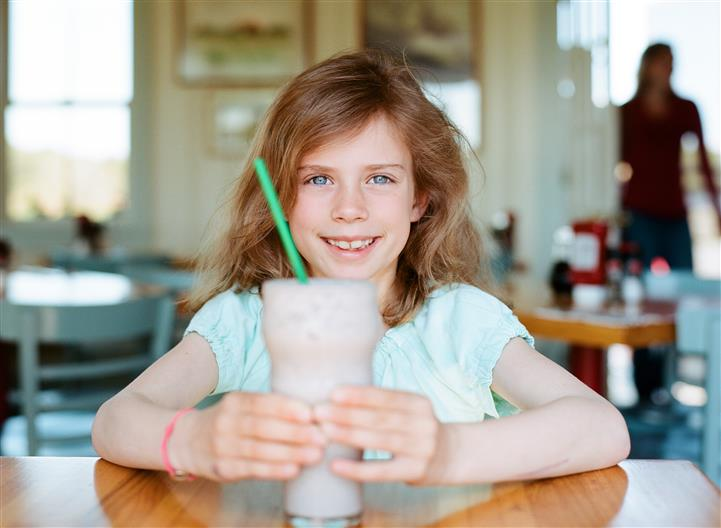 young child smiling at the camera holding a shake