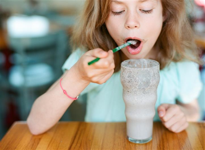 young child smiling at the camera holding eating a shake