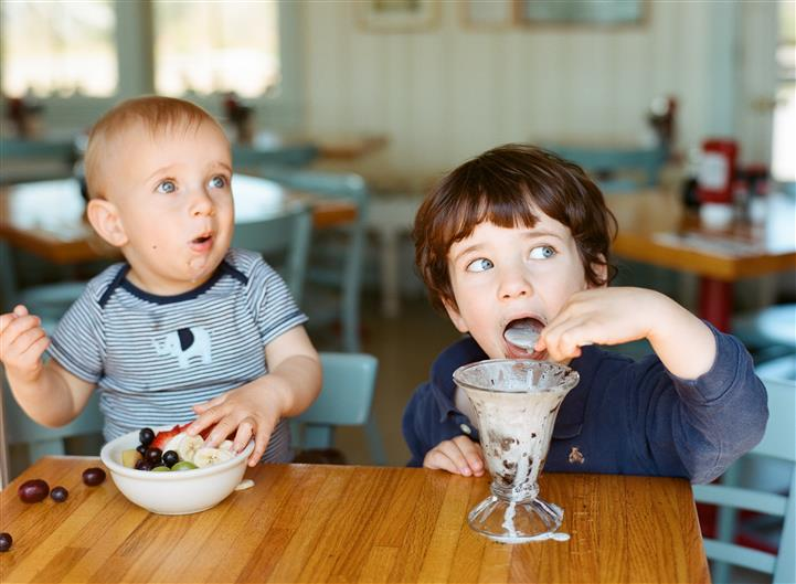 two young children eating food and desserts