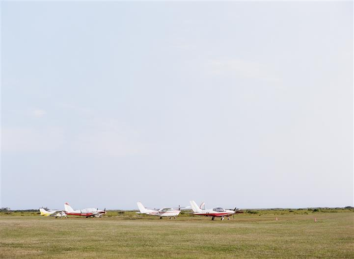 airport field with airplanes in the distance
