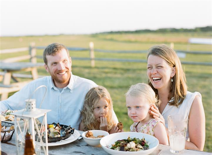 family sitting outdoors smiling and enkoying their food