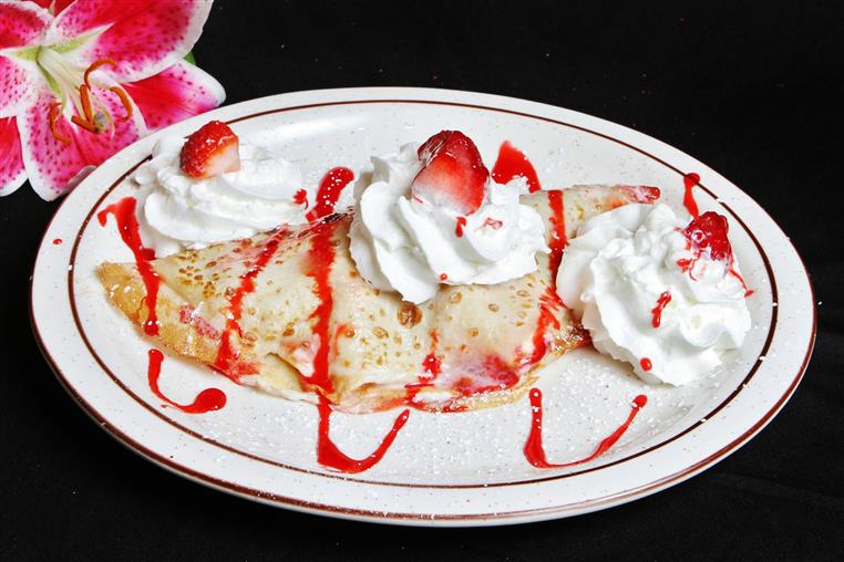 Crepe drizzled with strawberry sauce and topped with whipped cream