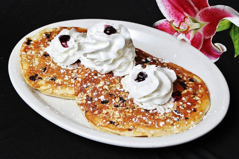 Blueberry pancakes on a plate with whipped cream