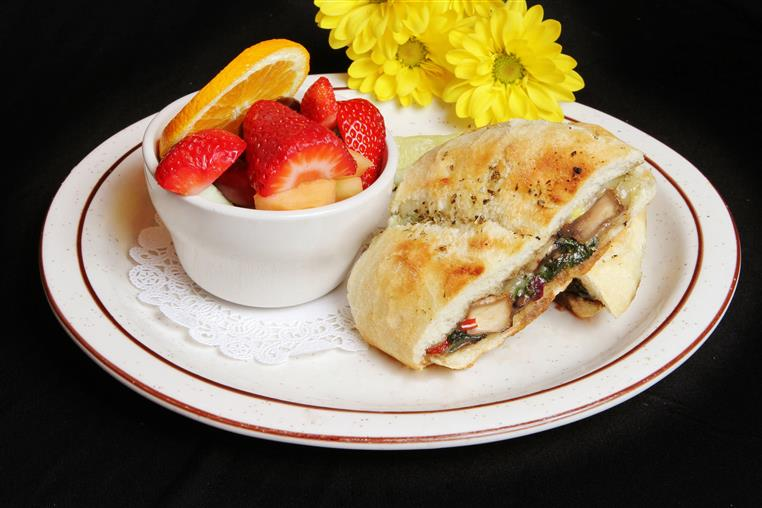 Grilled chicken panini with sliced strawberries and oranges in a bowl
