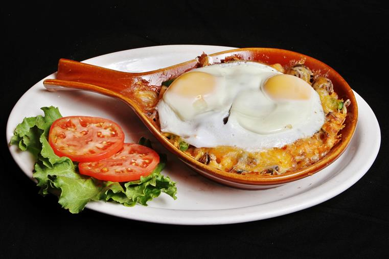 Breakfast skillet with two fried eggs on top with sliced tomatoes and lettuce