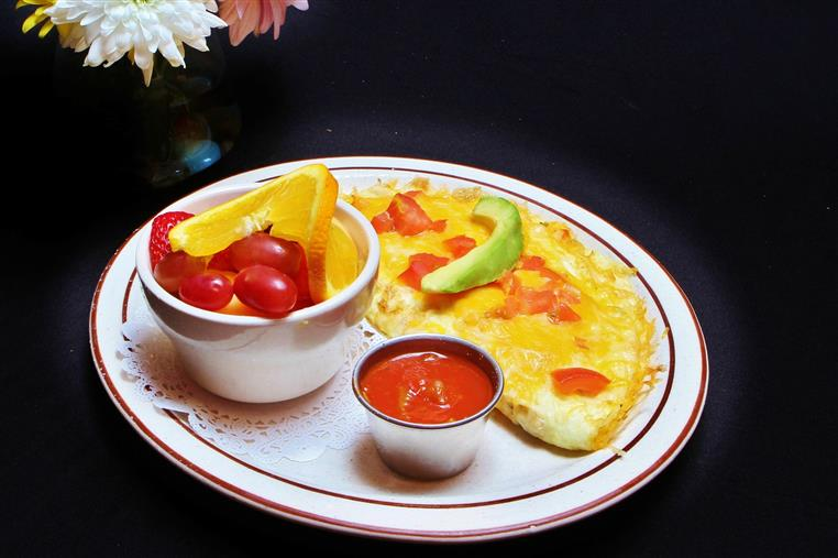 Cheese omelet with tomatoes and avocado with a small container of ketchup and a bowl of mixed fruit