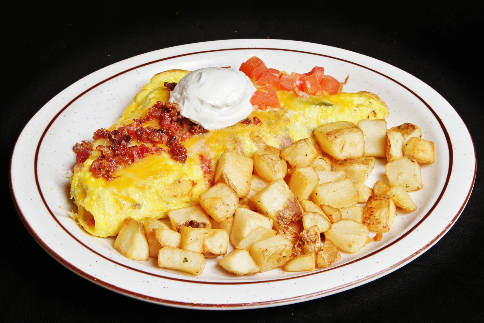 Omelet with crumbled bacon and diced tomatoes with sour cream and breakfast potatoes