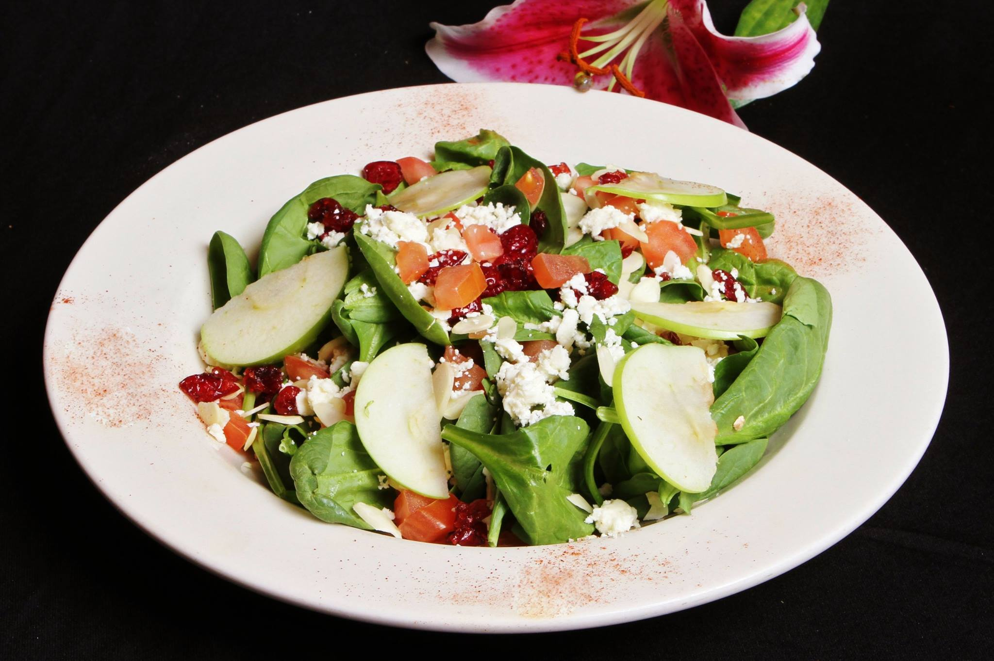 Mixed green salad with dried cranberries, feta cheese and sliced apples
