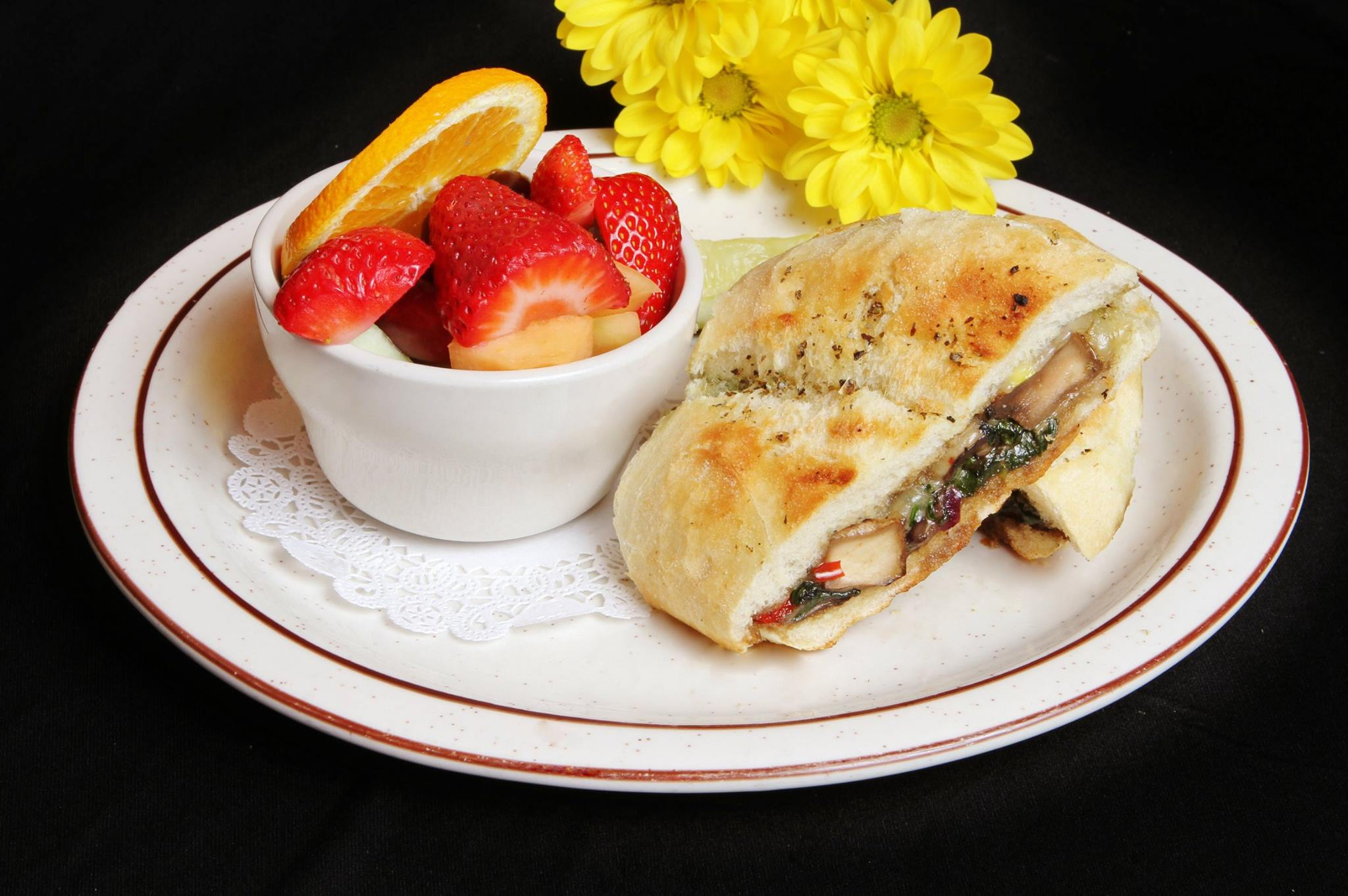 Grilled chicken panini with a bowl of sliced strawberries and oranges