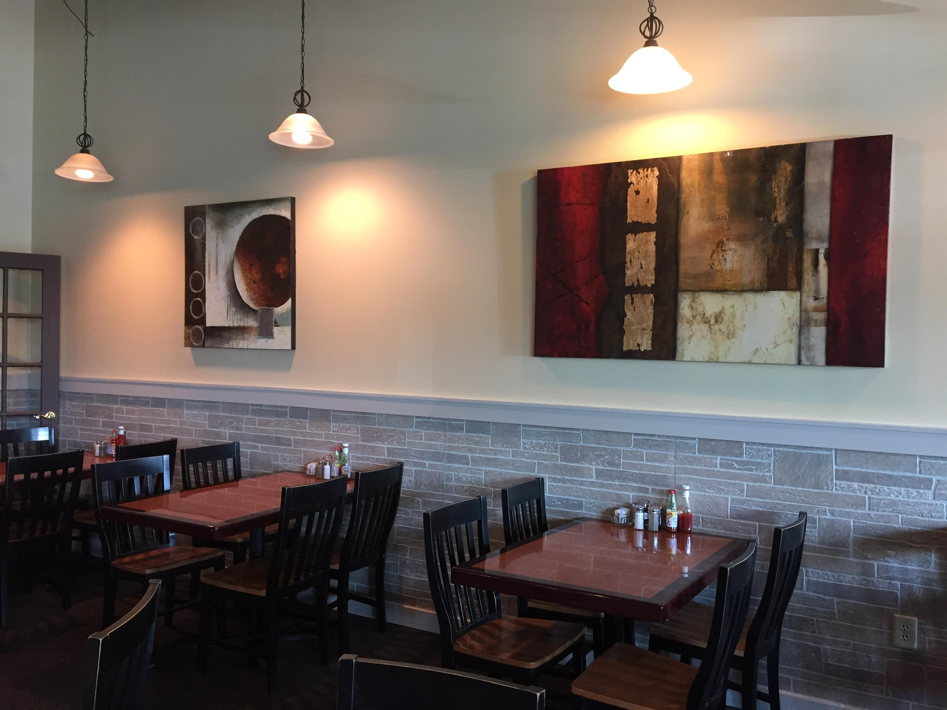 Interior dining area with wooden tables and chairs and abstract art on the walls