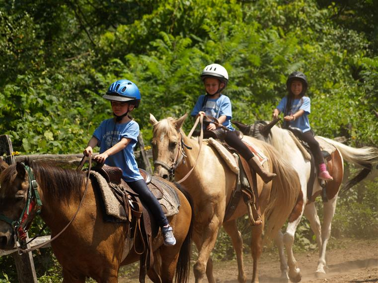 three children wearing helmets and riding horses