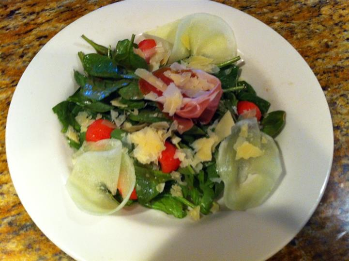 Salad with mixed greens toosed with vegetables, tomatoes and shredded cheese