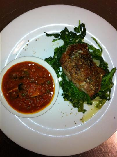 Meat cutlet over a bed of sauteed greens and served with a side of red sauce mixed with vegetables