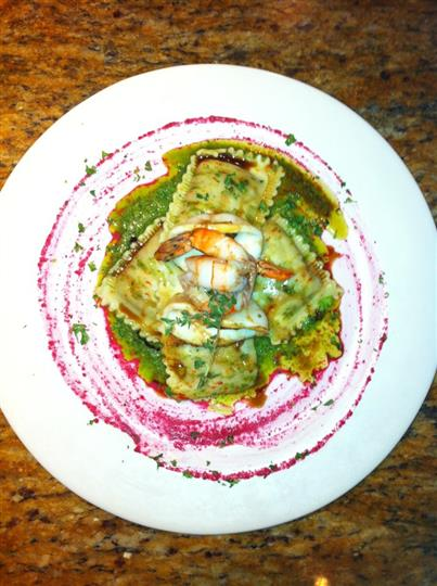 Ravioli dish topped with shrimp and covered in pesto sauce served in white plate