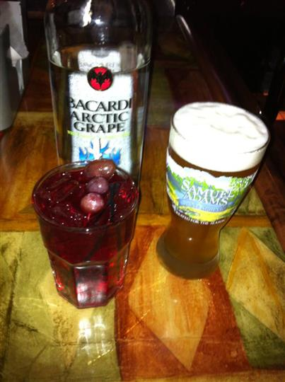 A glass of beer and a glass of a cocktail drink on the bar counter with a Bacardi bottle in the background
