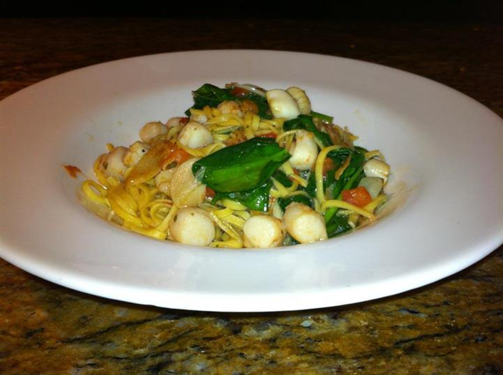Fettuccine pasta  tossed with scallops and basil leaves served in white deep dish