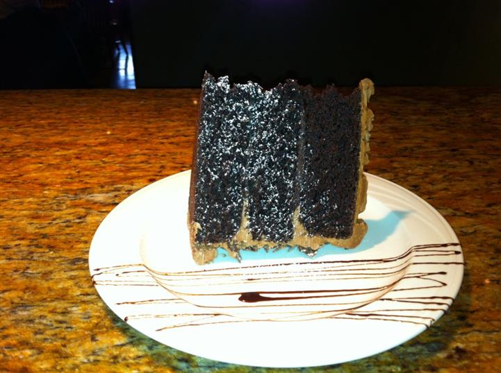Triple layer chocolate cake with chocolate frosting served in plate decorated with sauce