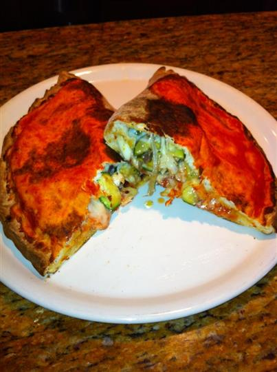 Vegetable calzone with melted cheese halved and served in white dish