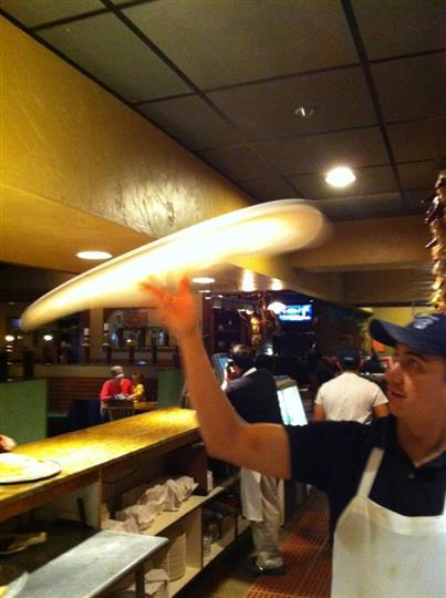 Man dressed in apron tossing dough for pizza in the kitchen
