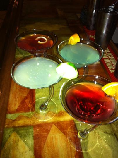 Colored cocktails served in Martini glasses with orange and lime wedges