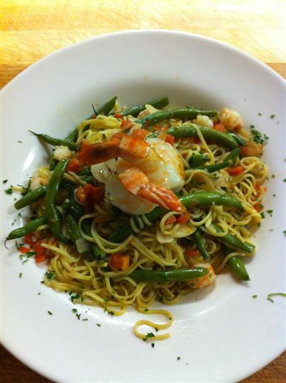 Seafood pasta dish with spaghetti tossed with vegetables and two shrimps on top